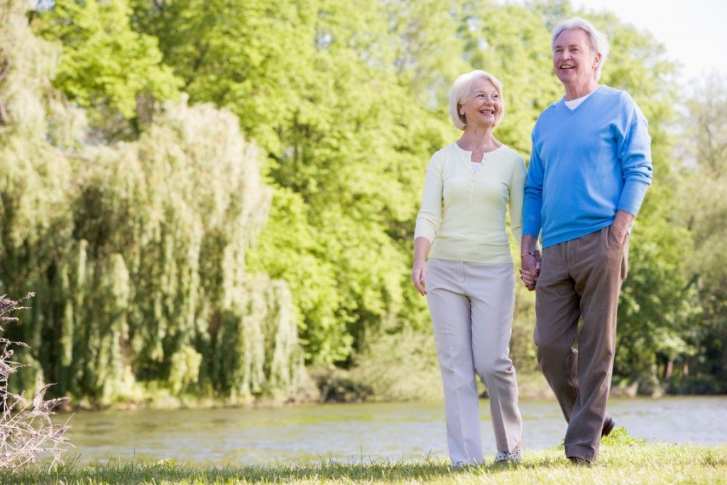 Couple walking outdoors at park by lake smiling